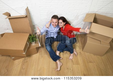 Happy American Couple Sitting On Floor Kissing Celebrating Moving In A New House