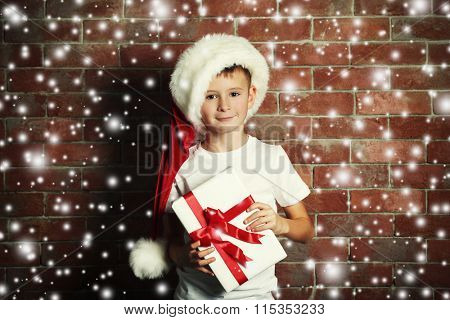 Cute little boy with gift box on brick wall background.