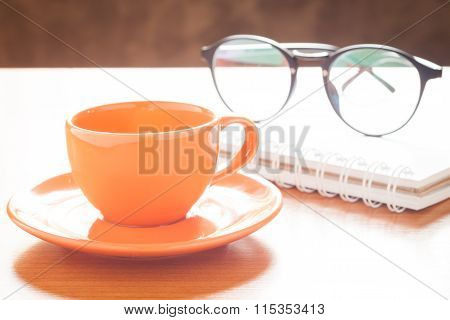 Close Up Of Coffee Cup With Book And Eyeglasses