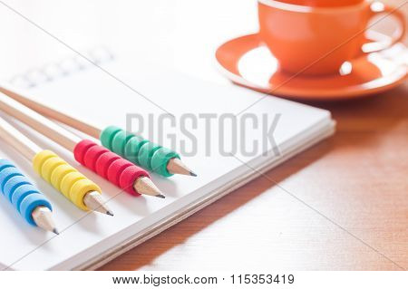 Pencils On Open Blank White Notebook With Coffee Cup On The Desk