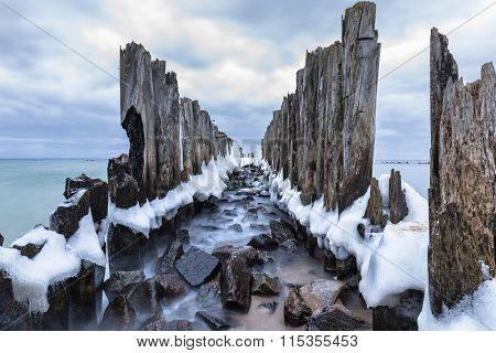Frozen wooden breakwaters line to the world war II torpedo platform at Baltic Sea, Babie Doly, Poland