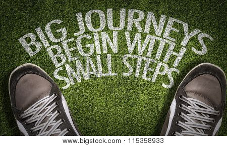 Top View of Sneakers on the grass with the text: Big Journeys Begin With Small Steps
