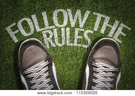 Top View of Sneakers on the grass with the text: Follow The Rules