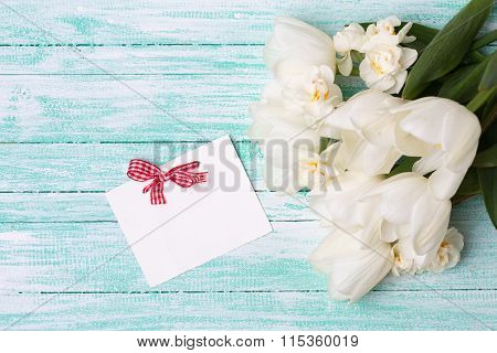 White Tulips And Daffodils  And Empty Tag On Turquoise Painted Planks.
