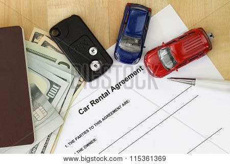 Car rental agreement next to car key, passport, cash and credit card