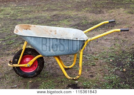 Dirty Metal Garden Wheelbarrow On Bare Ground