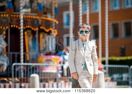 Stylish kid in a nice suit near the traditional French merry-go-round, Beauvais, France