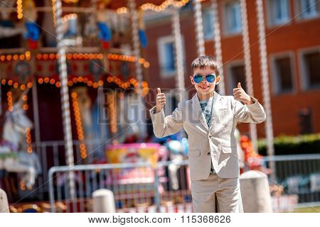 Stylish kid near the traditional French merry-go-round showing thumbs up, Beauvais, France