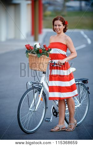 Young elegantly dressed woman with bicycle and a basket full of flowers