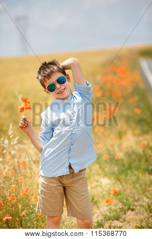 Cute smiling boy holding bouquet of poppies outdoors
