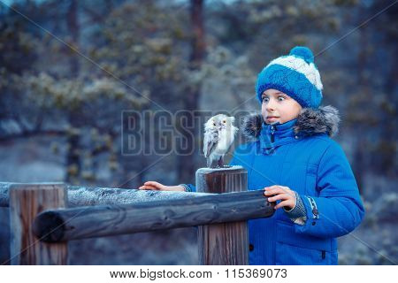 Cute boy with owl toy in winter forest