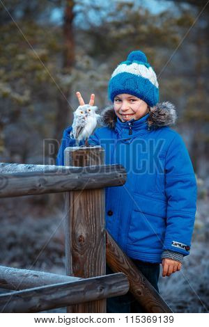 Cute boy with owl toy on shoulder in winter forest