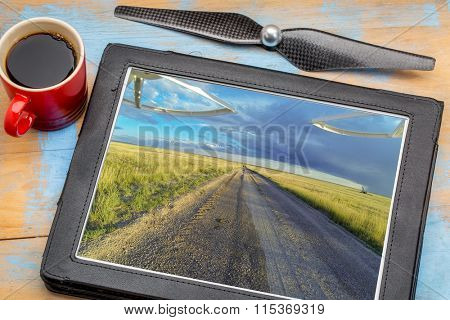 aerial landscape photography concept - reviewing aerial pictures of  a prairie in Colorado on a digital tablet with a drone propeller and coffee, screen picture copyright by the photographer