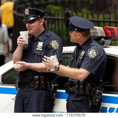 Two Police Officers While Drinking A Cup Of Coffee In Nyc.