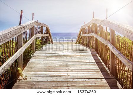 Wooden path over sand dunes with ocean view