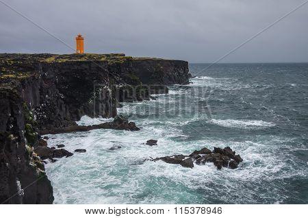 Orange Lighthouse On The Black Rock Cliff  Of Western Icelandic Coast, Snaefellsnes Peninsulain, Ice