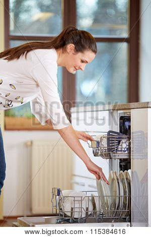 Young Woman Empty Out The Dishwasher