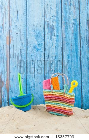 Colorful beach bag with toys at the beach