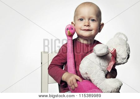 Smiling baby girl 1-2 year old having fun on white. Looking at camera with toys
