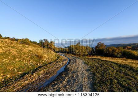 Rural Road In Autumn Landscape. Mountain Rural Road With Water And Mud, Blue Sky At The Horizon And