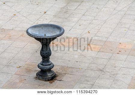 Metal Fountain In City. Drinking Metal Fountain With No Water With Orange Leaves Arround In City On