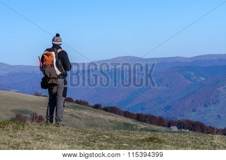 Happy Young Man Standing On Mountain.  Happy Young Tourist Man With Backpack Standing On Rocky Cliff