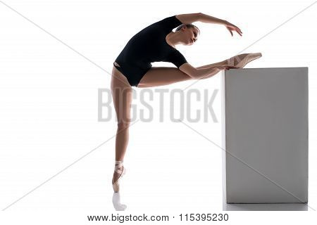 Ballerina putting her leg on cube while warming up