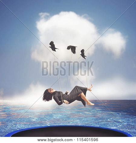 a woman being carried by birds over a trampoline in the ocean toned with a retro vintage instagram effect app or action