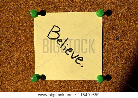 A Sticky Note Attached To A Cork Board With The Word 'Believe' Written On It
