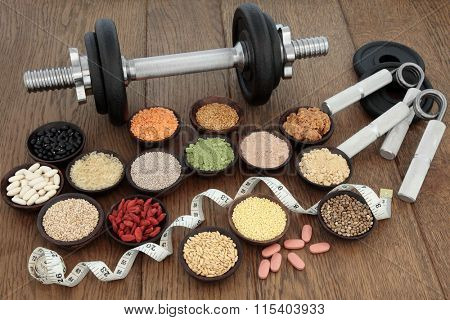 Body building equipment with dumbbells and hand grippers with health and super food  including supplement powders, ginseng vitamin pills, pulses, seeds, nuts, grains and tape measure.