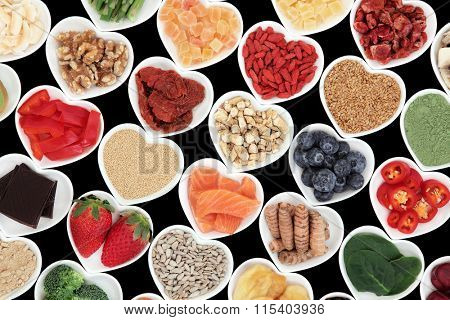Super food vegetable and fruit selection for good health in heart shaped porcelain dishes over black background, high in vitamins and antioxidants.