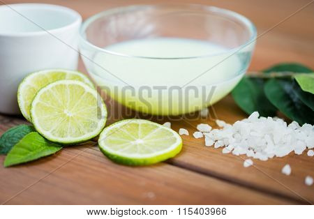 close up of body lotion in bowl and limes on wood