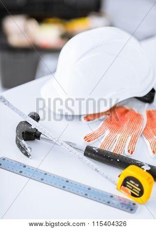 blueprint, flexible ruller, helmet and hammer