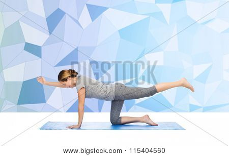 woman making yoga in balancing table pose on mat