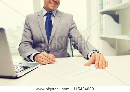 close up of businessman with laptop and papers