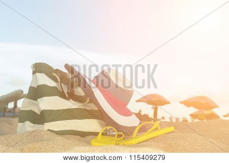 Summer concept of straw hat, bag, sunglasses and flip flops on a tropical beach.