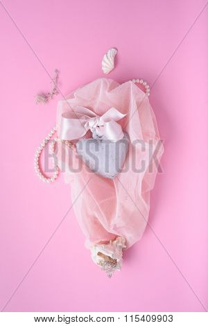 Valentines day pink background: heart, silk ribbon, shells on a veil. Romantic greeting card design.
