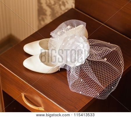 white hat with net veil and wedding shoes