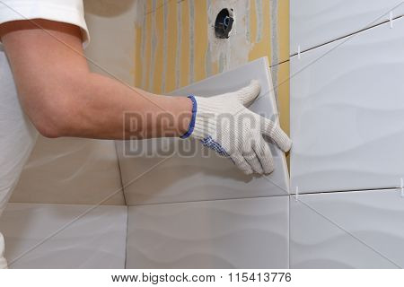construction work laying tile on the wall