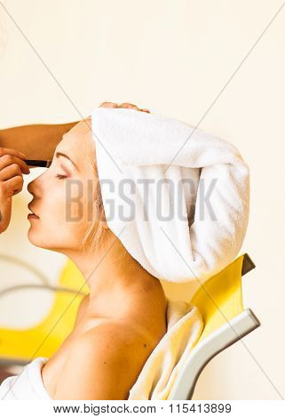 Stylist applying make-up to young beautiful woman