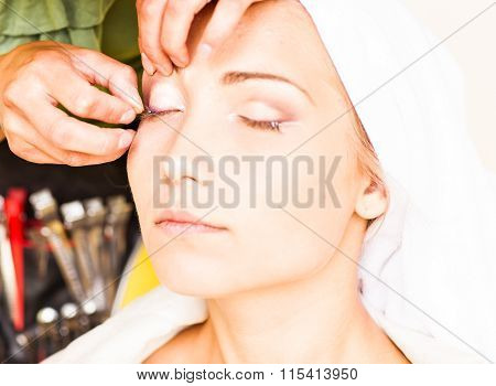 Makeup artist glues eyelashes. Beautiful woman face. Perfect makeup. Beauty fashion. Eyelashes. Cosm