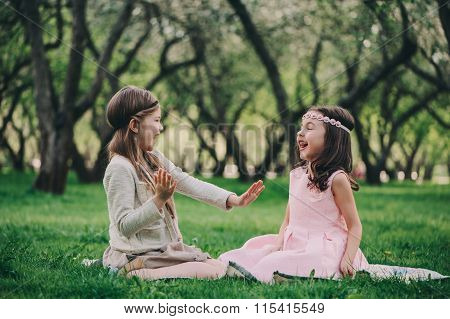 two happy little girlfriends in spring garden. Kid sisters spending time together outdoor an