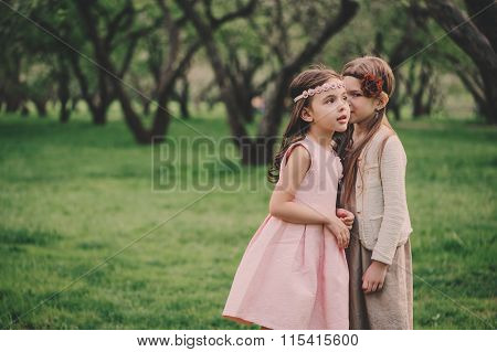 two kid girlfriends telling secrets to each other in spring park. Little dressy sisters spending tim