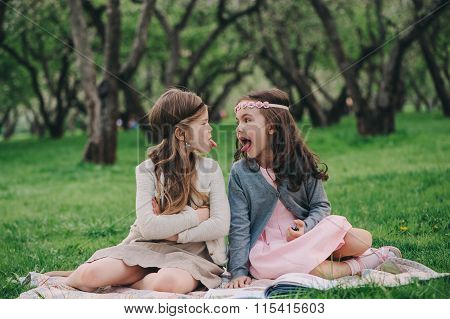 two kid girlfriends showing tongue to each other on the walk in spring. Upset angry sisters. Outdoor