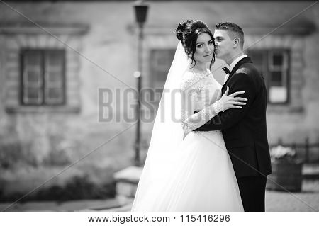 Handsome Groom Kissing Smiling, Beautiful Bride In The Street B&w