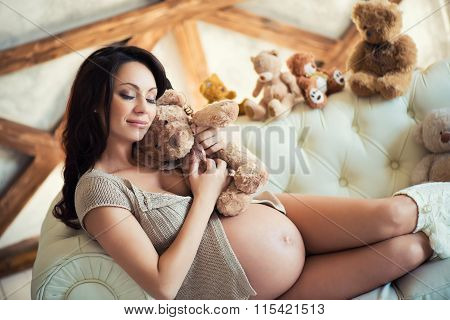 Pregnant Girl With Brown Teddy Bear Sitting On The Couch. Love And Motherhood