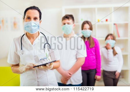 Female doctor and patient teenagers looking at camera, wear protective masks.Medical examination.