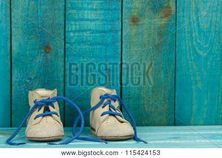 Baby Shoes On Turquoise Wooden Background.