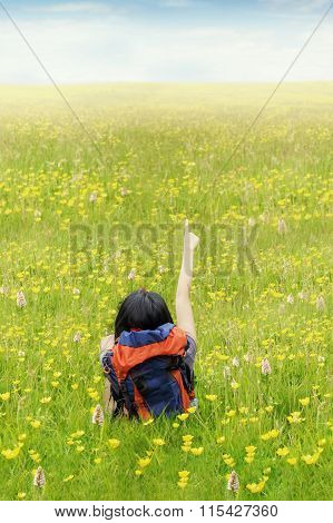 Backpacker Pointing On Meadow