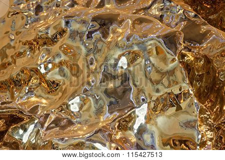 Liquid Metal Reflective Sculpture Closeup In A Warm Light